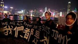 People wearing masks depicting Jimmy Sham hold a banner during an anti-government protest in Hong Ko