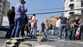 Lebanese demonstrators block the way in front of a car on the Beirut-Tripoli highway, near the town