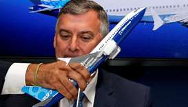 A model of a Boeing 737 MAX is held in front of Kevin McAllister, Boeing Commercial Airplanes CEO, d