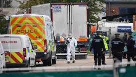 British Police officers in forsensic suits work near a lorry, found to be containing 39 dead bodies,