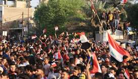 Iraqi protestors wave national flags during an anti-government demonstration in the Shiite shrine ci