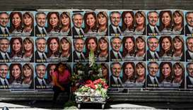 A woman sells flowers under a political propaganda of Argentina's President and presidential candida