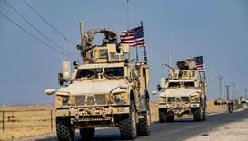 US military vehicles, part of a convoy arriving from northern Iraq, drive through the countryside of
