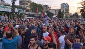 Lebanese anti-government protesters shout slogans during a demonstration in Beddawi town on the outs