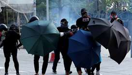 Anti-government demonstrators take cover under umbrellas during a protest in Hong Kong