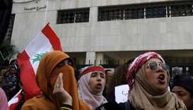 Lebanese protesters chant slogans as they take part in an anti-government demonstration in front of