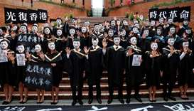 University students wearing Guy Fawkes masks pose for a photoshoot of a graduation ceremony to suppo