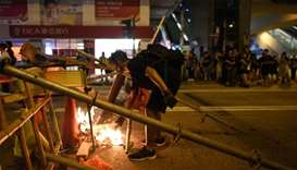 A protester setting fire to a barricade in the street during a stand off with police near the Mongko