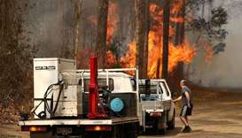A local resident is seen near a bushfire burning next to Busbys Flat Road in Busbys Flat, Australia
