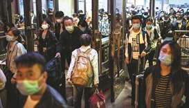 "People wearing facemasks arrive at the Beijing Railway station after the country's national ""Golden"