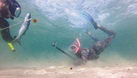 A Palestinian spear-fisherman holds a fish while diving underwater in the Mediterranean Sea off the