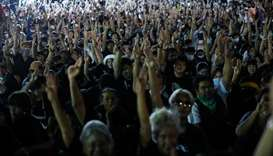 Pro-democracy demonstrators flash the three-fingers salute as they gather during a Thai anti-governm