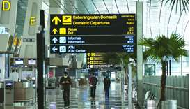 Airline and airport staff walk though the nearly empty Soekarno-Hatta International Airport in Jakar