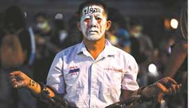 A pro-democracy protester in chains and make-up is seen during a demonstration at a road intersectio