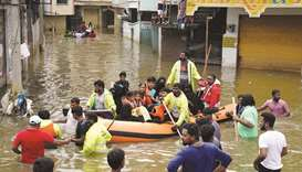 Residents are evacuated from a flooded neighbourhood after heavy rainfall in Hyderabad yesterday.60