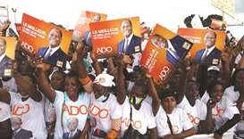 Supporters of presidential candidate Alassane Ouattara of the ruling RHDP coalition party hold signs
