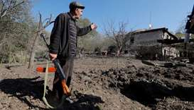 Local resident Alexei Agadzhanov holds a rifle while showing a crater following recent shelling in t