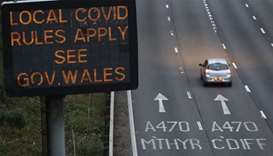 Traffic passes a COVID-19 sign displayed along the M4 motorway in southeast Wales as further restric
