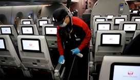 A staff member of Japan Airlines wearing a protective face mask and gloves cleans the cabin of a pla