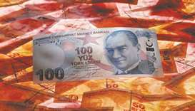 A 100 Turkish lira banknote is seen on top of 50 Turkish lira banknotes in this picture illustration