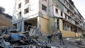 Workers remove debris near a residential building, which was damaged during the military conflict ov