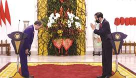 Japan's Prime Minister Yoshihide Suga and Indonesian President Joko Widodo greet each other after a