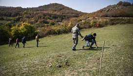 Members of the Karabakh Ministry of Emergency Situations search for unexploded cluster bombs on the