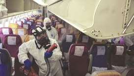 Workers in protective suits spray inside an aircraft during a disinfection process in Thailand. No t