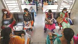 Women wearing protective face masks travel in a suburban train in Mumbai yesterday. Authorities resu