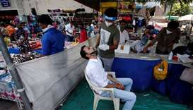 A healthcare worker takes swab from a man for a rapid antigen test in a market area, amidst the Covi