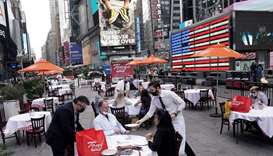 Servers deliver food to a table at a pop up restaurant set up in Times Square in New York