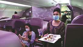 A Singapore Airlines stewardess smiles while serving food in business class during the inaugural lun