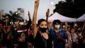 Pro-democracy protesters hold up the three-finger salute outside Bangkok Remand Prison in Bangkok on