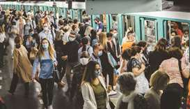 Commuters wearing protective face masks boarding and exiting a train at Saint-Lazare metro railway s