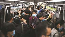 Passengers wearing face masks ride the subway in Beijing on October 23. Only China and India saw gai