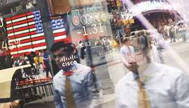 People are reflected in the window of the Nasdaq MarketSite in Times Square. In a week where benchma