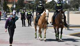 Police patrol on horseback along the St Kilda Esplanade in Melbourne on October 26