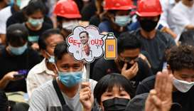 A pro-democracy protester holds a sign with the image of Thailand's Prime Minister Prayut Chan-O-Cha