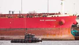 A military boat passes in front of the Liberia-flagged oil tanker Nave Andromeda at Southampton Dock