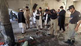 A member of a bomb disposal team surveys the site of a bomb blast at a religious seminary in Peshawa