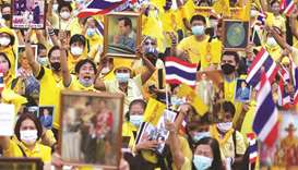 Royalists wearing yellow shirts wave Thailand's flags during an event to support the monarchy in Ban