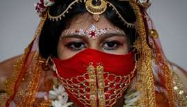 Sarayna Biswas, 6, wearing a face mask and dressed as Kumari wearing gold, takes part in a ritual du