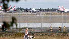 A woman walks her dog past a British Airways Boeing 747 G-CIVD plane at London Heathrow airport, one
