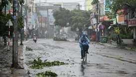 A man rides along a deserted road amid strong winds in central Vietnam's Quang Ngai province on Octo