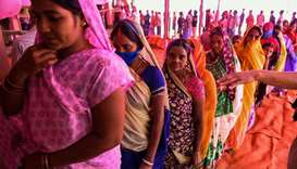 Voters queue up to cast their ballots for Bihar state assembly elections at a polling station in Mas