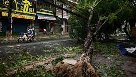 A family rides on a scooter past uprooted trees in central Vietnam's Quang Ngai province in the afte