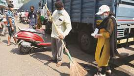 A man sweeps a road as a punishment for not wearing a face mask and failing to pay fine for it amid