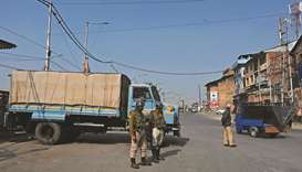 Government forces stand guard at a check point during a one-day strike called by the All Parties Hur