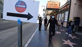 People walk on Hollywood Boulevard outside the Pantages Theater polling station, during the global o