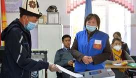 A man wearing a national 'Ak-kalpak' hat and a face mask casts his ballot at a polling station durin